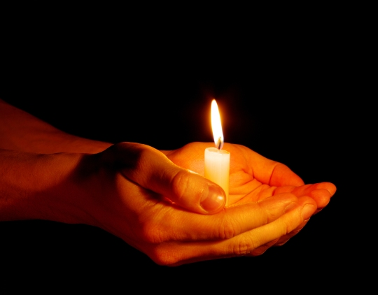 bigstock-candle-in-a-hand-19600874